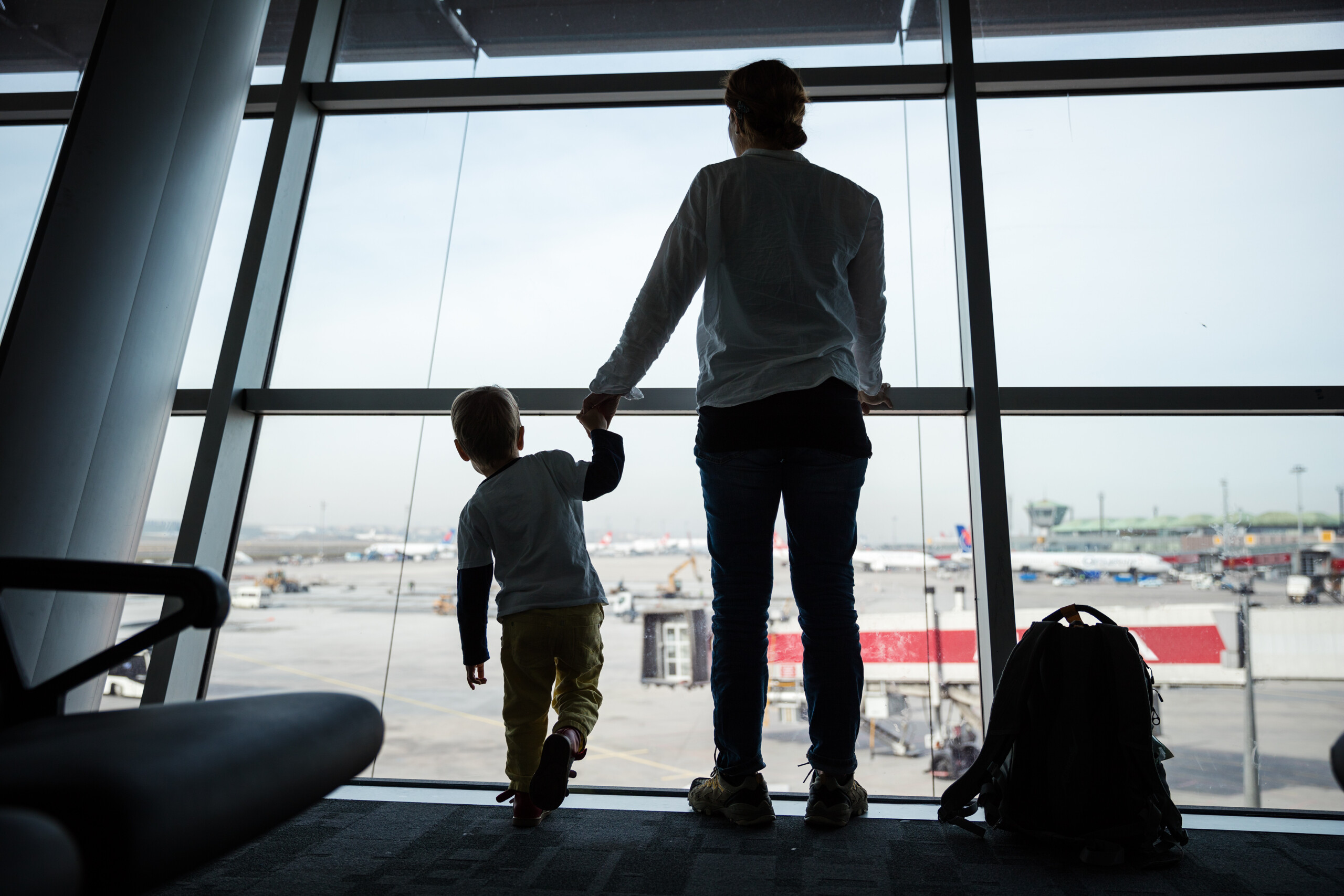 mother-and-son-standing-near-window-in-airport-and-PF6CSVE